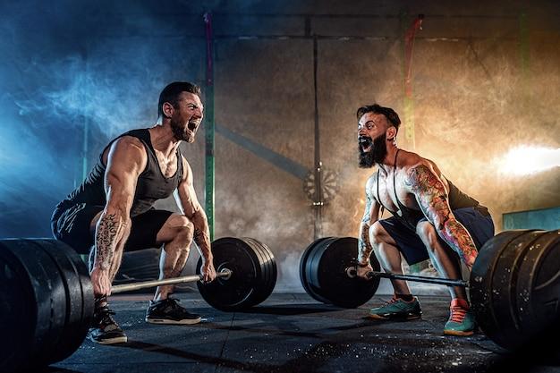 Dwóch Mięśni Brodaty Tattoed Sportowców Trenujących Na Siłowni Premium Zdjęcia