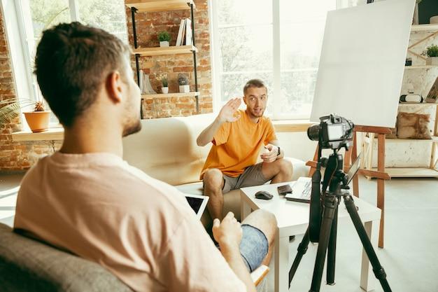 Dwóch Młodych Blogerów Rasy Kaukaskiej W Zwykłych Ubraniach Z Profesjonalnym Sprzętem Lub Kamerą Nagrywającą Wywiad Wideo W Domu Darmowe Zdjęcia