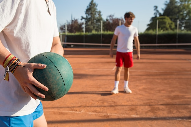 Dwóch profesjonalnych tenisistów rozgrzewa ub, rzucając sobie piłką lekarską. Premium Zdjęcia