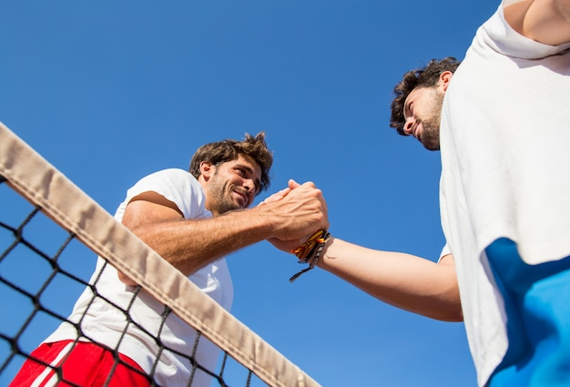 Dwóch profesjonalnych tenisistów trzymających ręce nad siatką tenisową po meczu. Premium Zdjęcia