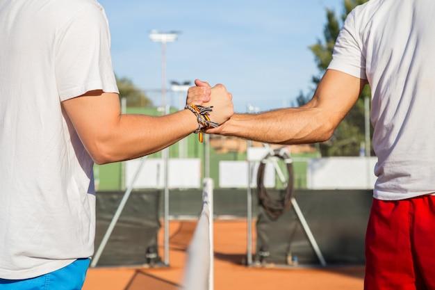 Dwóch profesjonalnych tenisistów trzymających ręce nad siatką tenisową przed meczem. Premium Zdjęcia