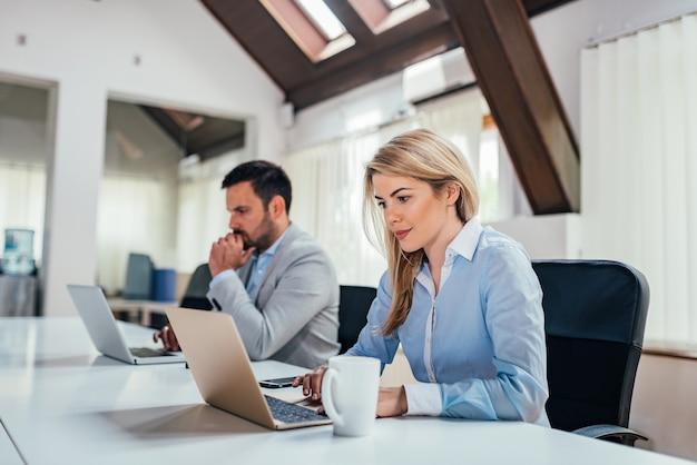 Dwóch przedsiębiorców pracujących na komputerach przenośnych w jasnym biurze coworkingowym. Premium Zdjęcia