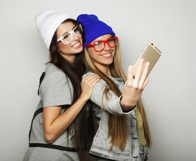 Dwóch Przyjaciół Nastoletnich Dziewcząt W Stroju Hipster Zrobić Selfie Nad Białym Premium Zdjęcia