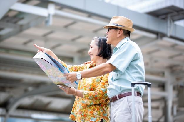 Dwóch starszych azjatów podróżujących z mapą i bagażem przed budynkiem Premium Zdjęcia