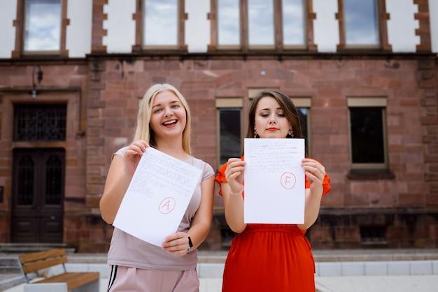 Dwóch Studentów W Pobliżu Uniwersytetu Z Wynikami Testów Premium Zdjęcia