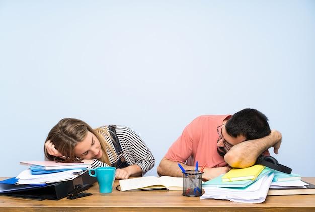 Dwóch studentów z wieloma książkami i spaniem Premium Zdjęcia