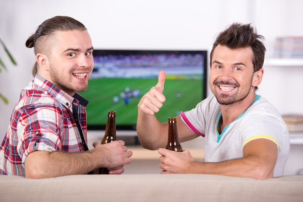 Dwóch szczęśliwych fanów piłki nożnej podczas oglądania ulubionej drużyny w telewizji. Premium Zdjęcia