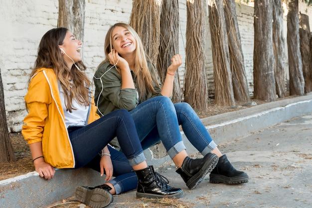 Dwóch szczęśliwych przyjaciół dzielących się słuchawkami, aby słuchać muzyki Darmowe Zdjęcia