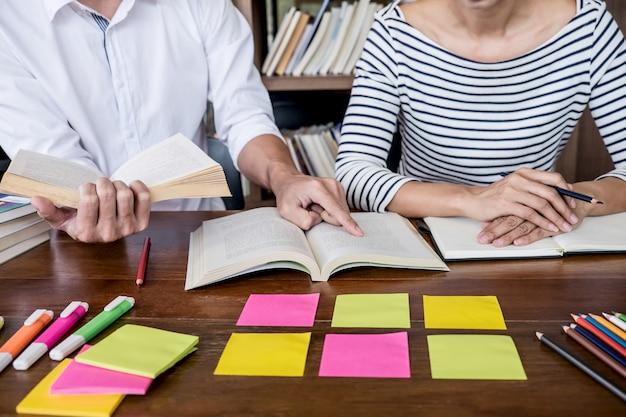 Dwóch uczniów lub grupa uczniów siedzących w bibliotece pomaga przyjacielowi w odrabianiu lekcji i odrabianiu lekcji Premium Zdjęcia
