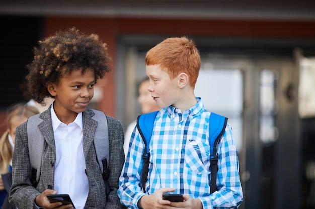 Dwóch Uczniów Z Telefonami Komórkowymi Premium Zdjęcia