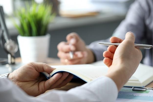 Dwóch Urzędników Omawiających Biznes Za Pomocą Notatników Premium Zdjęcia
