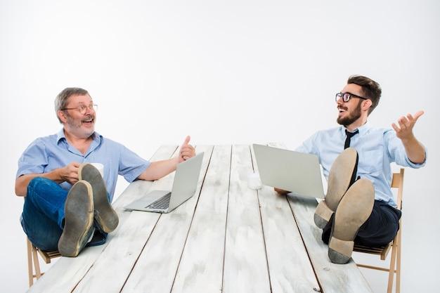 Dwóch Uśmiechniętych Biznesmenów Z Nogami Nad Stołem, Pracując Na Laptopach Na Białym Tle. Biznes W Stylu Amerykańskim Darmowe Zdjęcia
