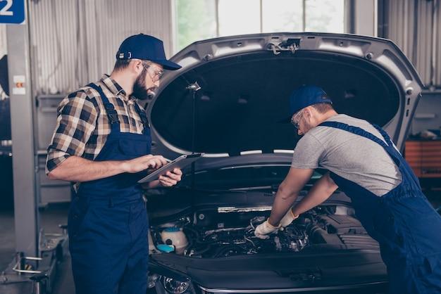 Dwóch Zapracowanych Mechaników W Warsztacie W Specjalnym Niebieskim Mundurze Premium Zdjęcia