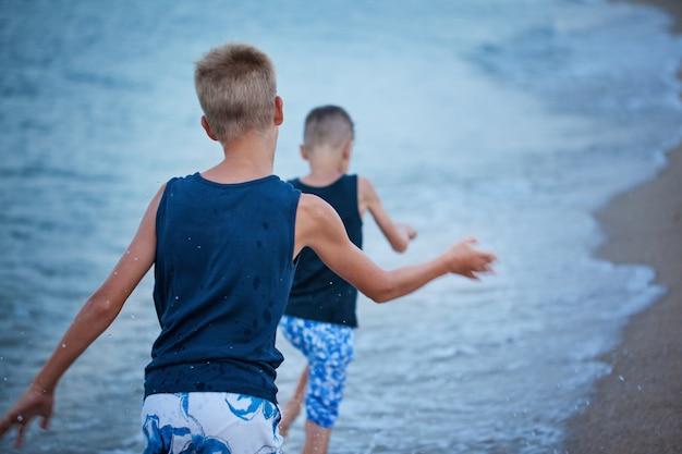 Dwoje dzieci chłopców chodzących na lato plaża morze, szczęśliwy najlepszych przyjaciół gra. Premium Zdjęcia
