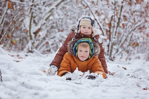 Dwoje małych dzieci, bracia chłopiec bawi się i leży w śniegu na zewnątrz podczas opadów śniegu. aktywny wypoczynek z dziećmi zimą w chłodne dni Premium Zdjęcia