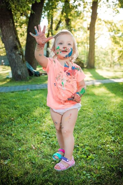 Dwuletnia Dziewczynka Poplamiona Kolorami Na Zielonym Trawniku Darmowe Zdjęcia