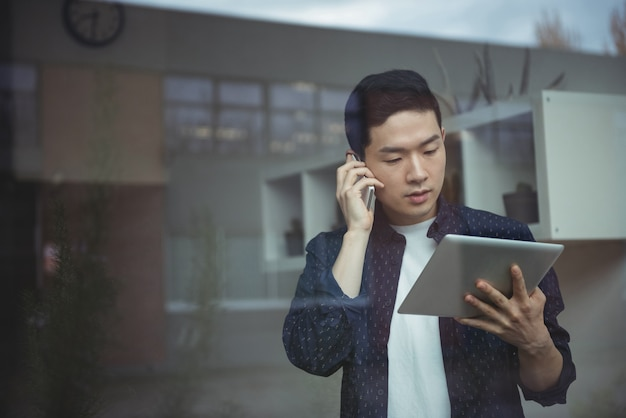 Dyrektor Wykonawczy Opowiada Na Telefonie Komórkowym Podczas Gdy Używać Cyfrową Pastylkę Darmowe Zdjęcia