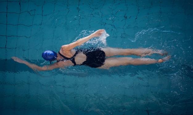 Dysponowana Kobieta Pływa W Basenie Premium Zdjęcia