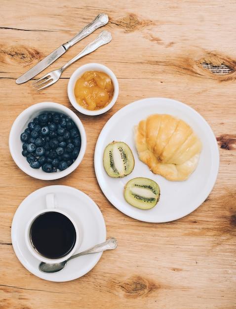 Dżem; jagody; kiwi; chleb i filiżanka kawy na drewniane teksturowanej tło Darmowe Zdjęcia