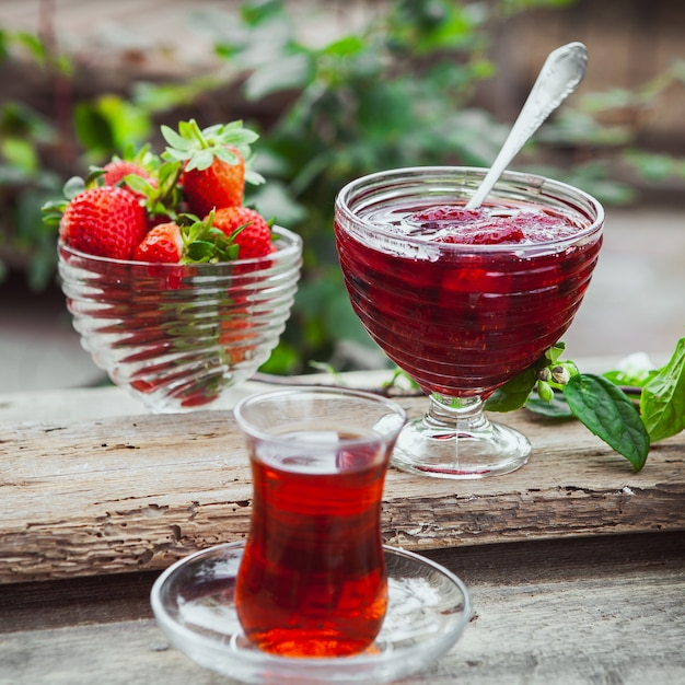 Dżem Truskawkowy W Talerzu Z łyżeczką, Herbatą W Szkle, Truskawkami, Zbliżenie Rośliny Na Drewnianym I Ogrodowym Stole Darmowe Zdjęcia