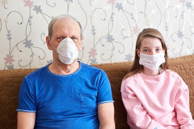 Dziadek I Wnuczka Poddani Kwarantannie W Maskach Medycznych. Samoizolacja Podczas Epidemii. Premium Zdjęcia