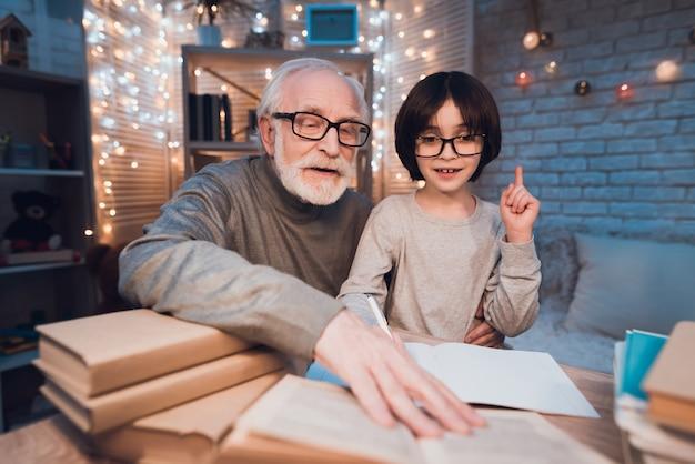 Dziadek Pomaga Wnukowi W Odrabianiu Lekcji Premium Zdjęcia
