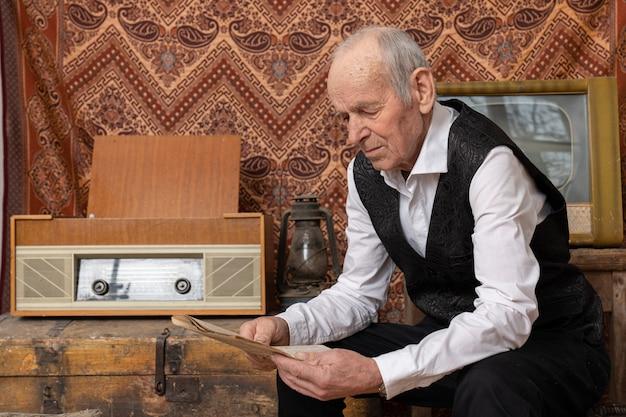Dziadek W Białej Koszuli Siedzi Przy Starym Radiu I Czyta Gazetę Premium Zdjęcia