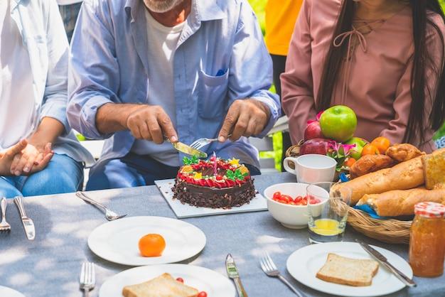 Dziadek Z Urodzinowym Tortem świętuje W Rodzinnym Przyjęciu W Domu Ogród Premium Zdjęcia