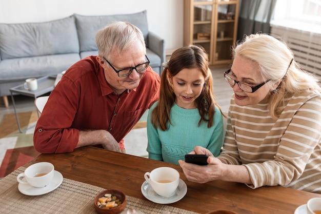 Dziadkowie I Dziewczyna Patrząc Na Telefon Darmowe Zdjęcia