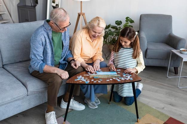 Dziadkowie I Dziewczyna Robi Puzzle Pełny Strzał Darmowe Zdjęcia