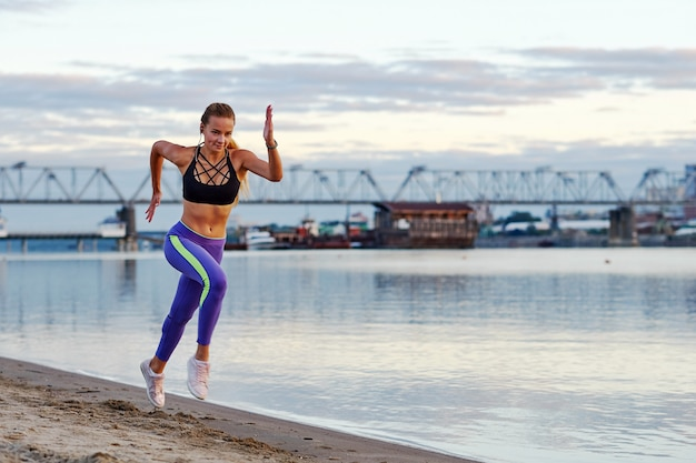 Działająca Kobieta W Piasku Przy Wschodem Słońca. Rano Jogging Na Plaży Lub Wybrzeżu Rzeki Na Tle Miasta Miejski Premium Zdjęcia