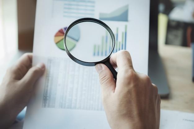 Działalności człowieka za pomocą powiększania do przeglądu rocznego bilansu przy użyciu komputera przenośnego do obliczania budżetu. audyt i kontrola integralności przed koncepcją inwestycyjną. Premium Zdjęcia