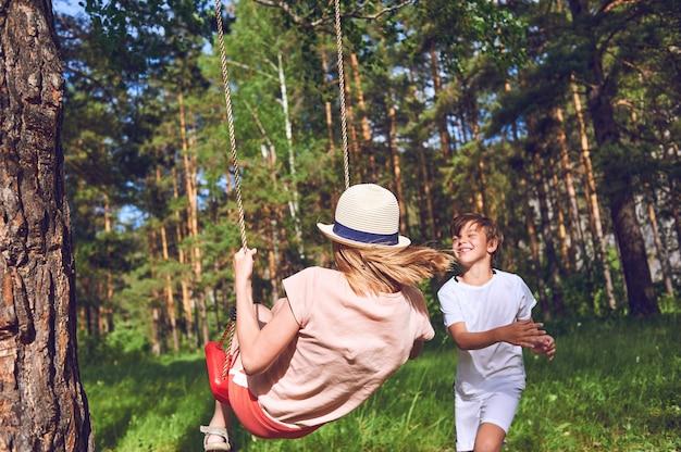 Dzieci Bawią Się I śmieją Z Natury. Chłopiec Potrząsa Dziewczyną. Zdjęcie Lifestyle Premium Zdjęcia