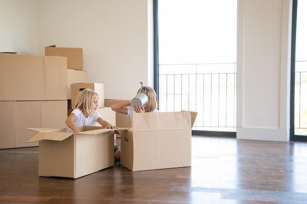 Dzieci Bawią Się Podczas Rozpakowywania Rzeczy W Nowym Mieszkaniu, Siadania Na Podłodze I Wyjmowania Przedmiotów Z Otwartych Kartoników Darmowe Zdjęcia