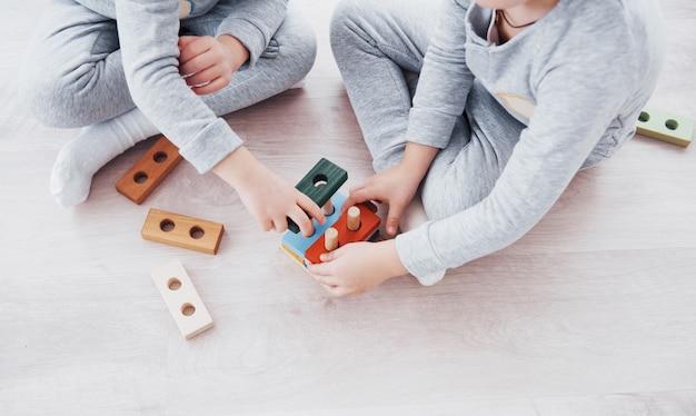 Dzieci Bawią Się Projektantem Zabawek Na Podłodze W Dziecięcym Pokoju. Dwoje Dzieci Bawiące Się Kolorowymi Klockami. Przedszkolne Gry Edukacyjne Darmowe Zdjęcia