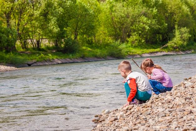 Dzieci Chłopiec I Dziewczynka Bawiące Się W Pobliżu Rzeki Premium Zdjęcia