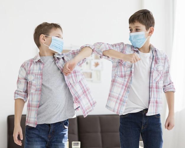 Dzieci Dotykają łokci Podczas Noszenia Masek Medycznych Darmowe Zdjęcia