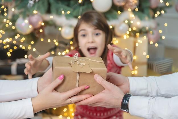 Dzieci-dziewczynki Rodzice Dają Prezenty Na Boże Narodzenie. Selektywna Ostrość. Wakacje. Premium Zdjęcia