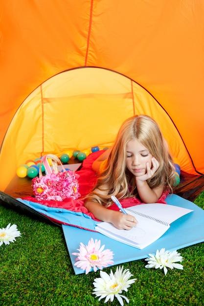 Dzieci Dziewczyny Writing Notatnik W Campingowym Namiocie Z Kwiatami Premium Zdjęcia