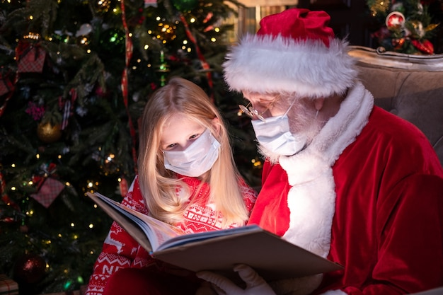 Dzieci I Mikołaj W Maskach Medycznych. Dziewczyna I święty Mikołaj Czytanie Książki Boże Narodzenie Siedzi W Pobliżu Bożego Narodzenia Premium Zdjęcia