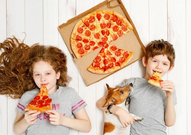 Dzieci I Pies Jedzący Pizzę Pepperoni Premium Zdjęcia