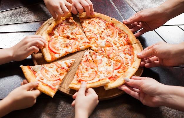 Dzieci jedzą pizzę w restauracji. Premium Zdjęcia