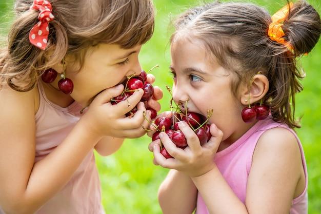 Dzieci Jedzą Wiśnie W Lecie Premium Zdjęcia