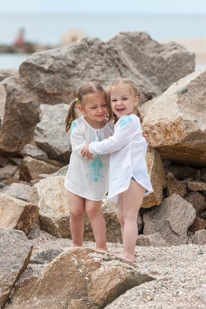 Dzieci Na Plaży Morskiej. Bliźniaki Stojące Przed Kamieniami I Wodą Morską. Darmowe Zdjęcia