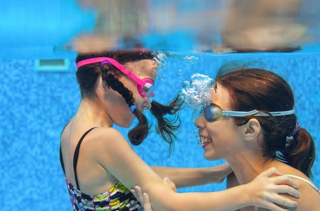 Dzieci Pływają W Basenie Pod Wodą, Szczęśliwe Aktywne Dziewczyny W Goglach Bawią Się W Wodzie, Dzieci Bawią Się Na Wakacjach Rodzinnych Premium Zdjęcia