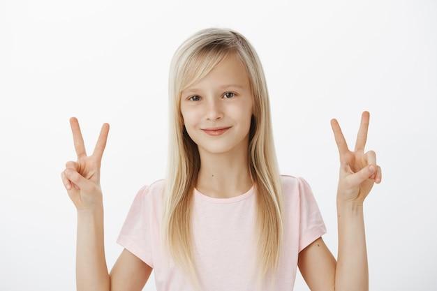 Dzieci Pokoju. Wzruszająca, Wesoła Młoda Dziewczyna Z Pozytywnym Nastawieniem, Uśmiechnięta Przyjaźnie I Obiema Rękami Pokazująca Znaki Zwycięstwa Lub V, Robiąca Zdjęcia Do Konkursu Dla Dzieci Na Szarej ścianie Darmowe Zdjęcia