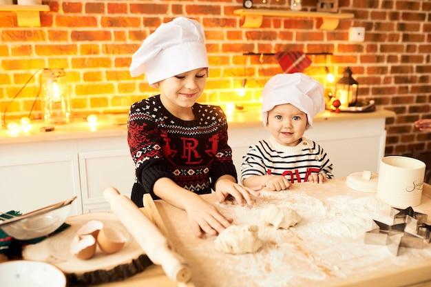 Dzieci są gotowane i bawione w kuchni mąką i ciastem Premium Zdjęcia