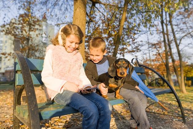 Dzieci Siedzą Na ławce W Parku Z Psem, Patrzą Na Smartfona Premium Zdjęcia