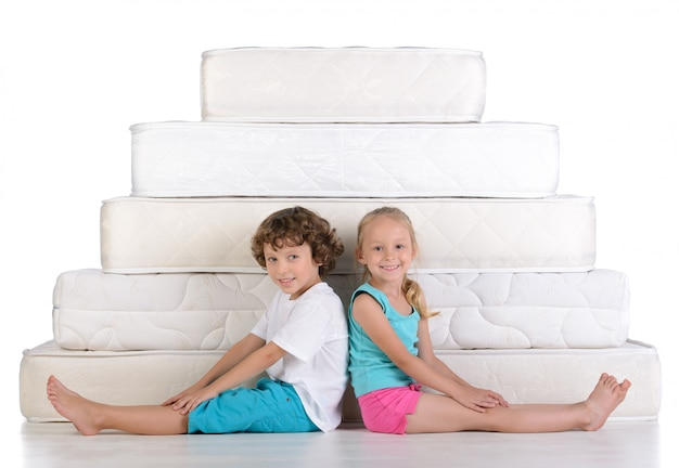 Dzieci siedzą przy białych materacach. Premium Zdjęcia