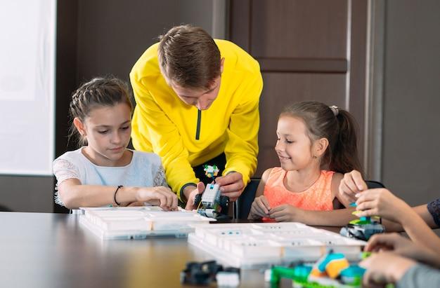 Dzieci tworzą roboty z nauczycielem. wczesny rozwój, majsterkowanie, innowacje, nowoczesna technologia. Premium Zdjęcia